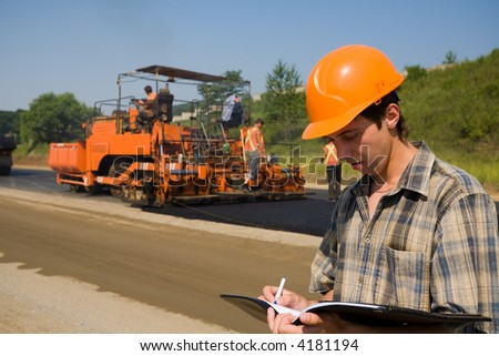 The road inspector on a working platform. Stacking of new asphalt.