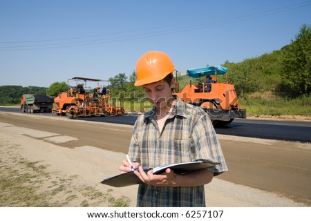 The road inspector on a working platform. Stacking of new asphalt.