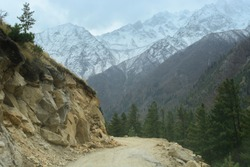 The road takes a sharp bend to reach the  last village on Indian side Chitkul before Tibet, which shows high mountains covered with snow.