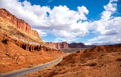 The road through the canyon on a clear day. Red rock canyon road in mountains. Canyon road landscape. Mountain road panorama