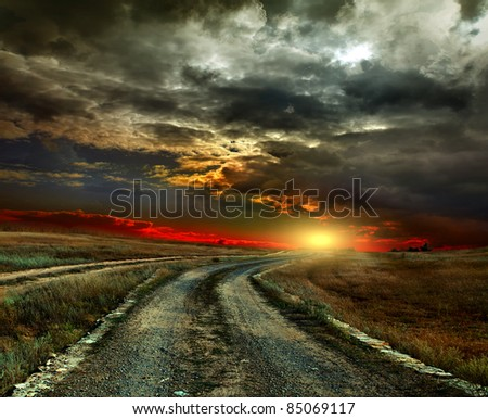 The road through the old grass field - stock photo