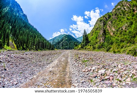 The road to the mountain gorge among the rocks. Mountain trail landscape. Trail in mountains. Trail to mountain gorge