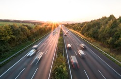The road traffic on a motorway at sunset .
