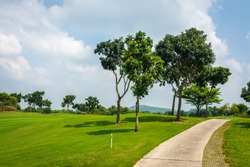 The road way for golf cart and golfer  in golf course with green grass ,green trees blue sky white clouds background.