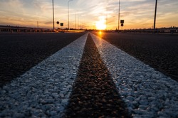 The road with a double continuous strip on the new asphalt with a small depth of field, blurred background and variable focus. Sunset, warm shades. Road construction concept. Place for text.