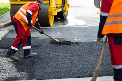 The road workers' working group updates part of the road with fresh hot asphalt and smoothes it for repair.