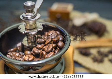 The roasted coffee beans in a coffee grinder with blur cinnamon and coffee beans background., #1166253358