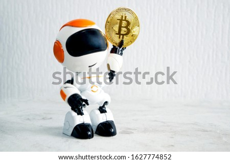 the robot holds a gold bitcoin in its hand, holding it up