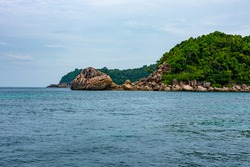 The rock island looks like a turtle. The rock is the head It has turtle-like eyes and mouth, the back is a tree like a turtle's shell. Located at Lipe island, Satun province, Thailand.
