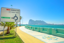 The Rock of Gibraltar, British territory, and its bay view from Spanish territory of La Linea town. directions road sign of Gibraltar center on the waterfront promenade.