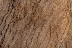The rocky background is copper brown. Rock. The texture of the rock, the background of the texture. Rock detail. Rock consisting of curves and smooth areas as a result of erosion effect.