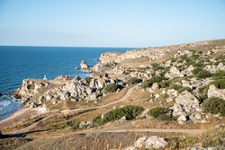 the rocky coast of the sea overgrown with grass descends to the sandy coast. There is a wave in the blue sea. On the horizon, water merges with the sky. Beautiful landscape for relaxation
