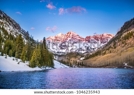 The Rocky Mountains near Aspen, Colorado glow in the light of the morning sunrise, as the mountains and trees reflect off the lake. #1046235943