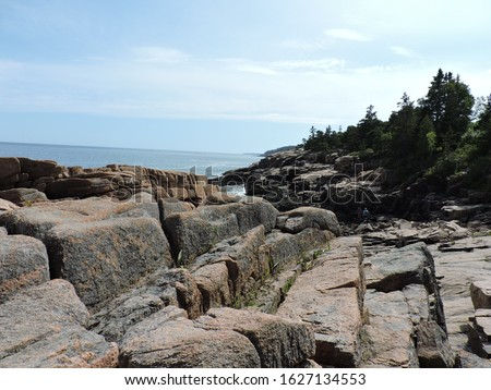 The rocky shoreline opens up to sea and waves beyond it. At times, angry waves relentlessly wear and weather these ancient rocks. On this day, all is calm.