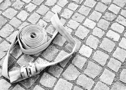 The rolled up fire hose over pavement background. Equipment for fire fighting. Desaturated photo