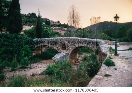 The Roman bridge across the Torrent de Sant Jordi at Pollenca in Mallorca at sunset.