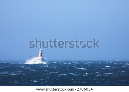 The roman styled lighthouse inside the bay at Simons Town, Western Cape, South Africa. Extremely windy day with choppy water and large waves breaking against the lighthouse.