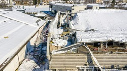 The roof collapsed under the weight of snow. Aerial view of damaged falling roof inside a publica city area. Large collapsed condominium or industrial company. View from above with a drone