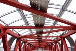 The roof is made of steel channels connected to each other. Red iron beams on bolts and rivets. Crosswalk, construction.