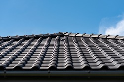 The roof of a single-family house covered with a new ceramic tile in anthracite against the blue sky, visible ceramic ventilation tile on the roof.