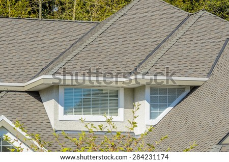 The roof of the house with nice window and white frame.