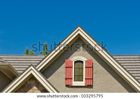 the roof of the house with nice window under the blue sky