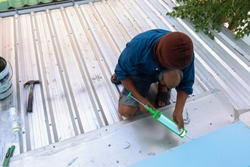 The roof repairman is firing silicone to fix the roof leaks. The photo is used for the advertisement of the house construction business.