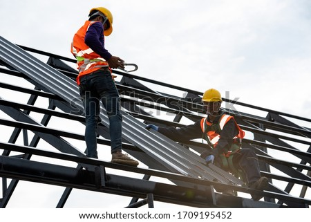 The Roofer technicians work on the roof structure of the building at the construction site. Roofer uses an electric drill and installs a metal sheet on the new roof. Photo stock ©