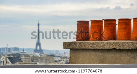 The roofs of Paris and its chimneys under a clouds sky, France, Europe