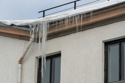 The roofs of the buildings are covered with snow and ice after a snowfall. Icicles hang from the facades of buildings. The fall of icicles carries a danger to people's lives. The frozen drainpipe
