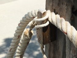 The rope in the white nylon is a circular loop that is attached to the wood.