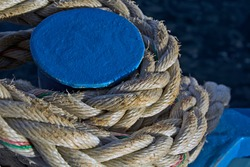 The rope that tied the boat to the blue metal pole on the shore at the marina.