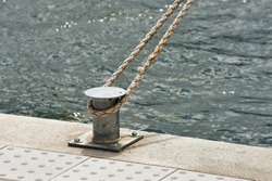 The rope that tied the boat to the metal pole on the shore at the marina