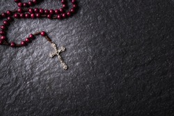 The rosary and the Christian cross lie on a dark granite stone.