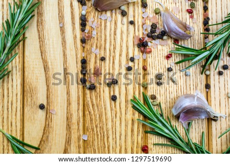 The rosemary, allspice, hot peppers, garlic cloves lie on a light brown background. #1297519690