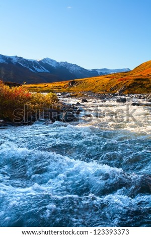the rough mountain river among glaciers in the evening
