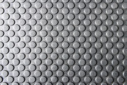 The round pattern texture on the rubber mats for the anti-slip purpose in the black and white scene.