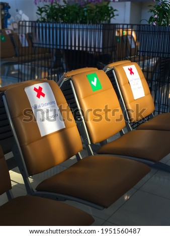 The row of brown chairs that show of sitting can sit and can not sit, management rule for new normal life while COVID-19 situation not yet finished at the airport. ストックフォト ©