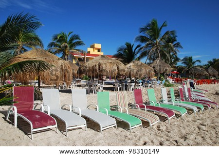 The row of colorful chairs on Mahahual resort town beach (Mexico).