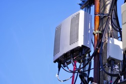 The RRU receives digital data and converts it to analog radio signals. It also receives radio signals and converts these to digital signals. Small Cell 4G, 5G Radio System with blue sky background.
