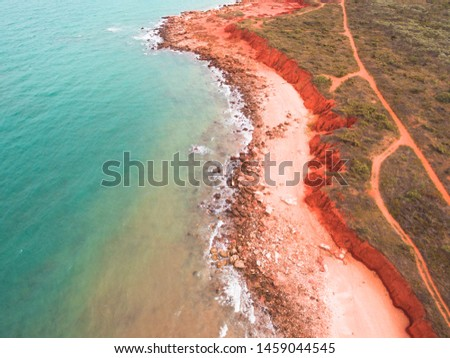 The rugged coastline of Reddell Beach in Broome, Western Australia as seen from the air with a drone. An outback road can be seen running parallel to the red cliffs, not far from the turquoise water.  #1459044545