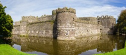 The ruins of Beaumaris Castle built in the 14th century by Edward the first as part of his military fortifications to conquer Wales. It is now a scheduled ancient monument