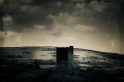 The ruins of Dolwyddelan Castle in Snowdonia National Park surrounded by bleak mountains and moorland. With a vintage, grunge edit