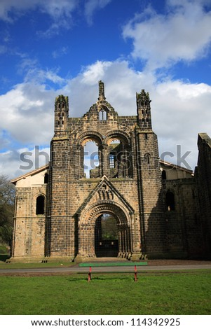 The ruins of Kirkstall Abbey against a blue sky