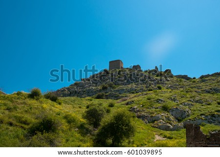 The ruins of medieval fortress of Acrocorinth up on the hill, the inner part is surrounded by old walls, on a bright sunny day, Peloponnese, Greece #601039895