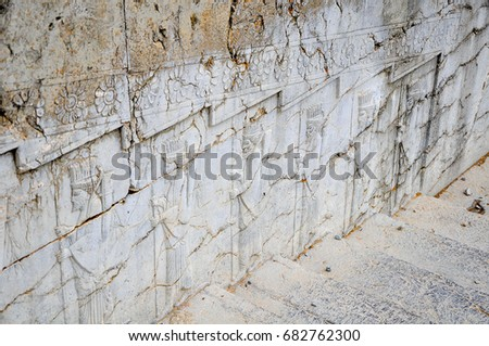 the ruins of the ancient Persepolis, ancient bas-reliefs decorating a wall along a ladder #682762300