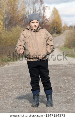 e8359f16084 The rural boy of 9 years on the country road in the fall.  1347154373