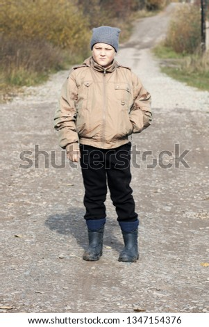 9bc4d4278b4 The rural boy of 9 years on the country road in the fall.  1347154376