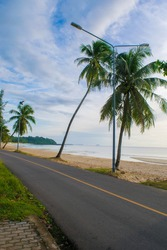 The rural road in front of the resort along the beach and sea with coconut tree and electricity post in the early morning and clear sky in the south of Thailand