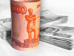 The Russian 5000 ruble bill is rolled up and stands upright. The background is black and white, includes bundles of 2000 and 200 rubles banknotes. Illustration about money, finance and business. Macro